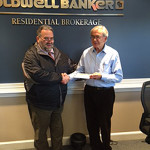 Ed Sanady, human services manager of The Town That Cares, accepts a Coldwell Banker Residential Brokerage Cares Foundation donation from David Bobowski, a sales associate affiliated with the Coldwell Banker Residential Brokerage West Hartford office.